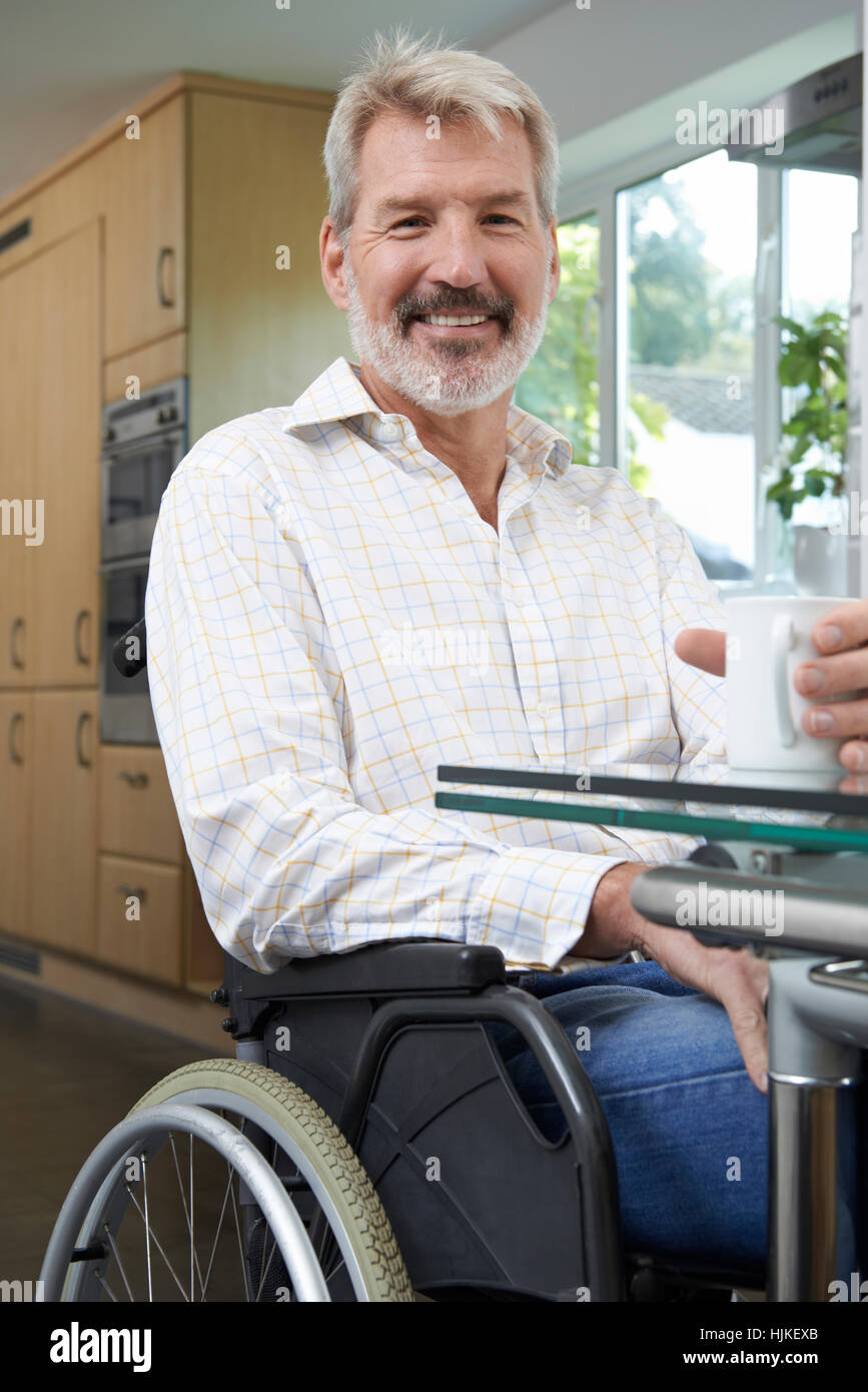Mature Disabled Man At Home With Hot Drink - Stock Image