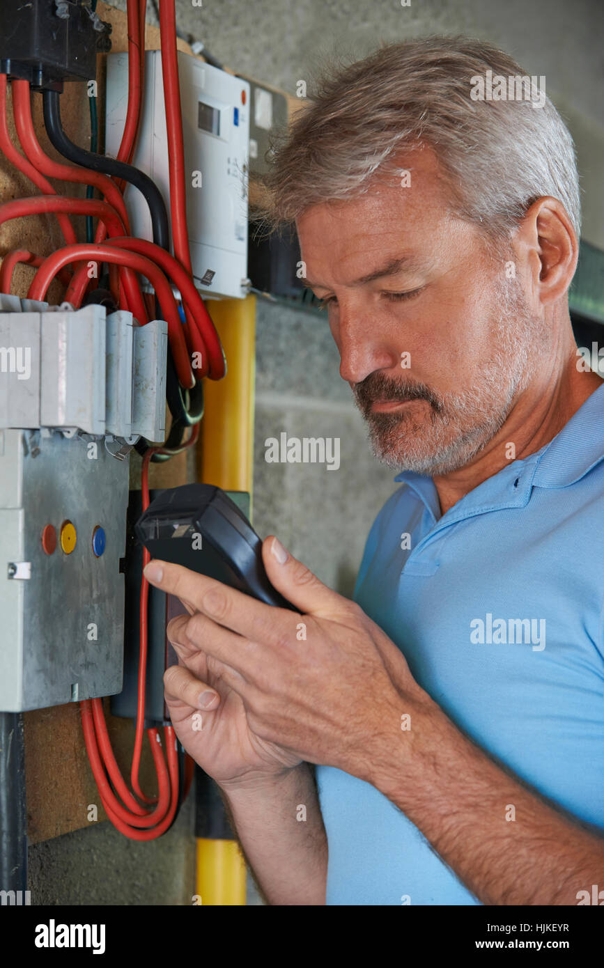 Man Taking Reading From Electricity Meter - Stock Image