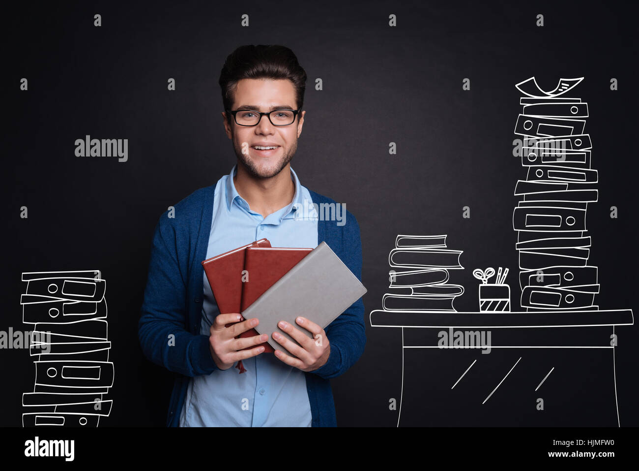 Joyful young man holding diaries. - Stock Image
