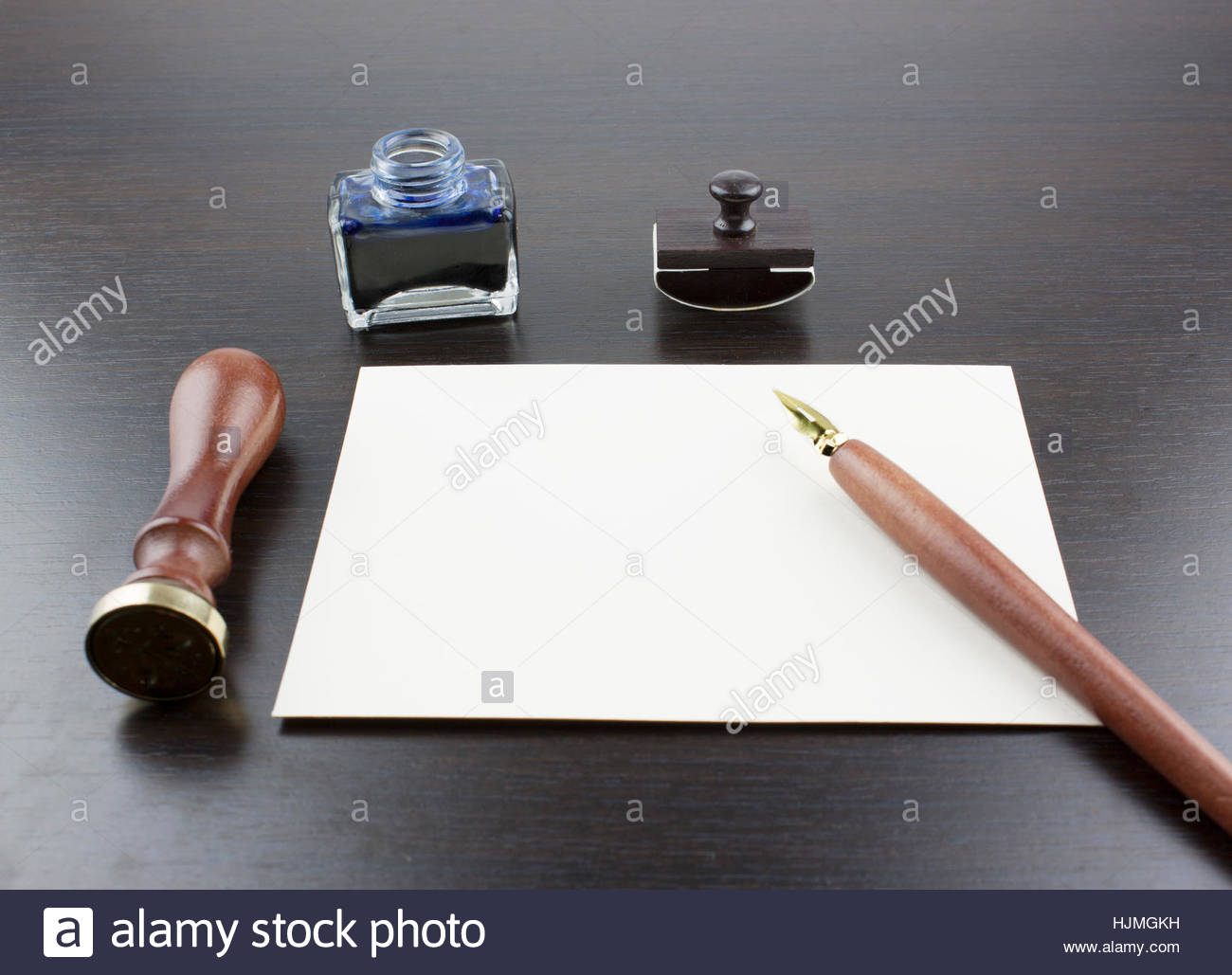 Pens, ink pot, papyrus and blotting paper on a brown table Stock Photo