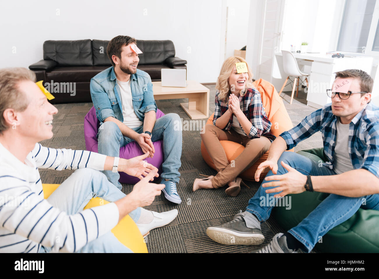 Happy cheerful people sitting in the beanbag chairs - Stock Image