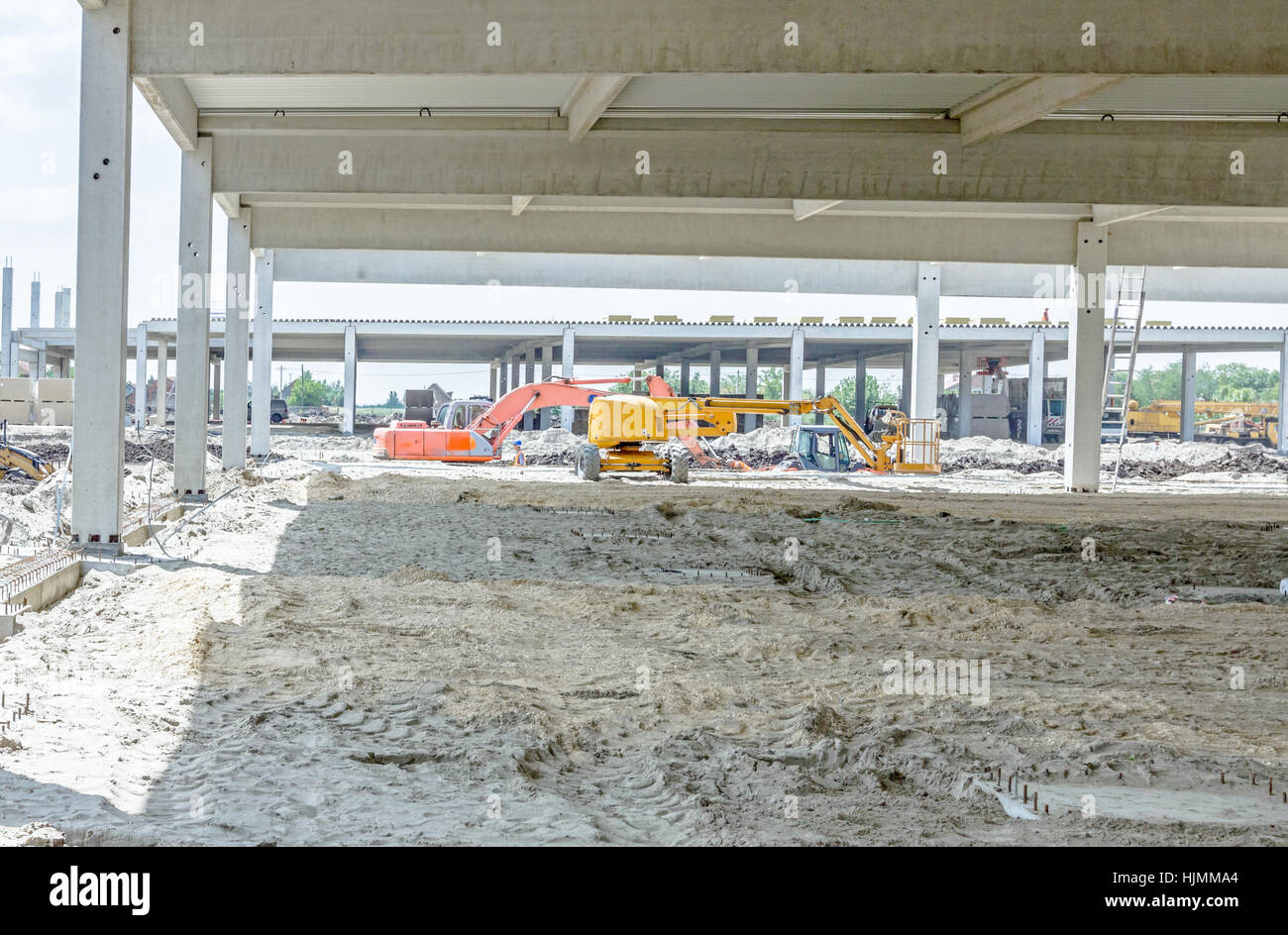 View on construction site with machinery, people at work. Landscape transform into large urban area, concrete hall. - Stock Image