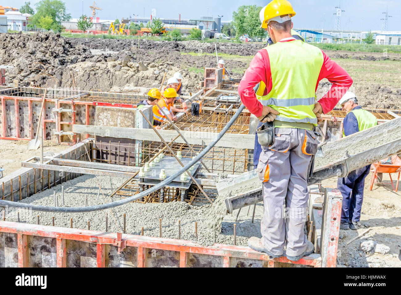Zrenjanin, Vojvodina, Serbia - May 29, 2015: Workers at building site are pouring concrete in mold from mixer truck. Stock Photo