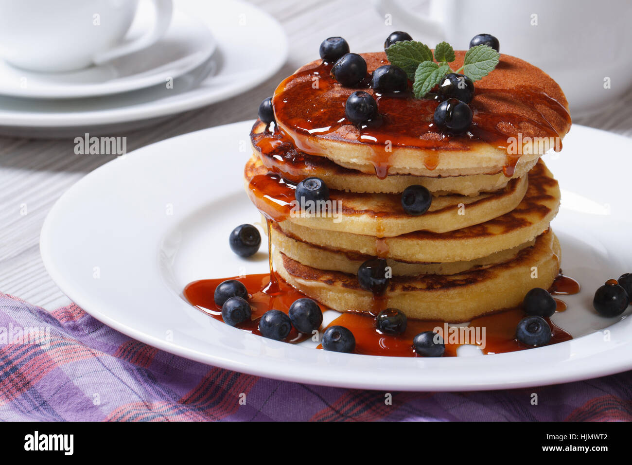 American Pancake with blueberries and maple syrup on a white plate horizontal - Stock Image