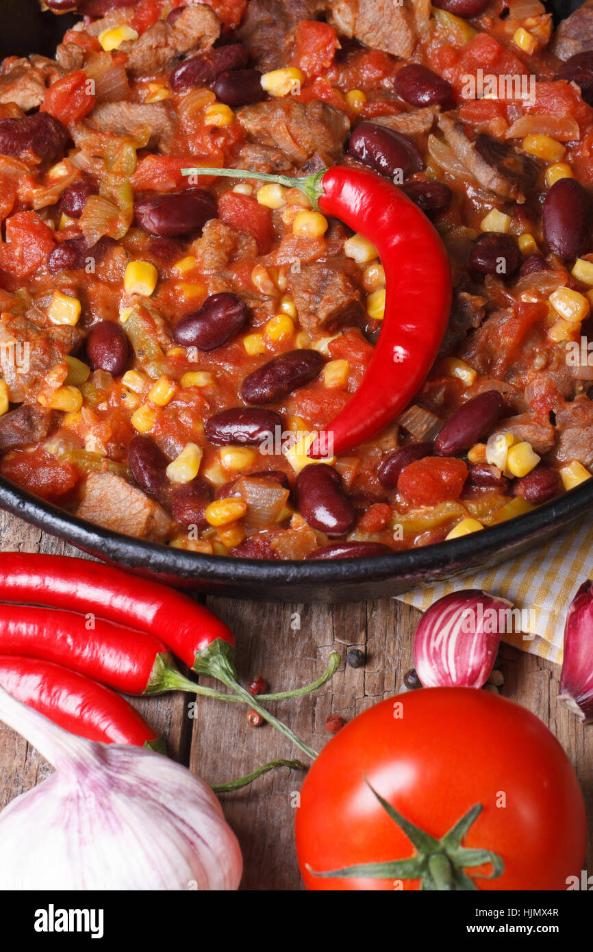 Mexican chili con carne close-up in a frying pan on a wooden background with the ingredients. vertical view from - Stock Image