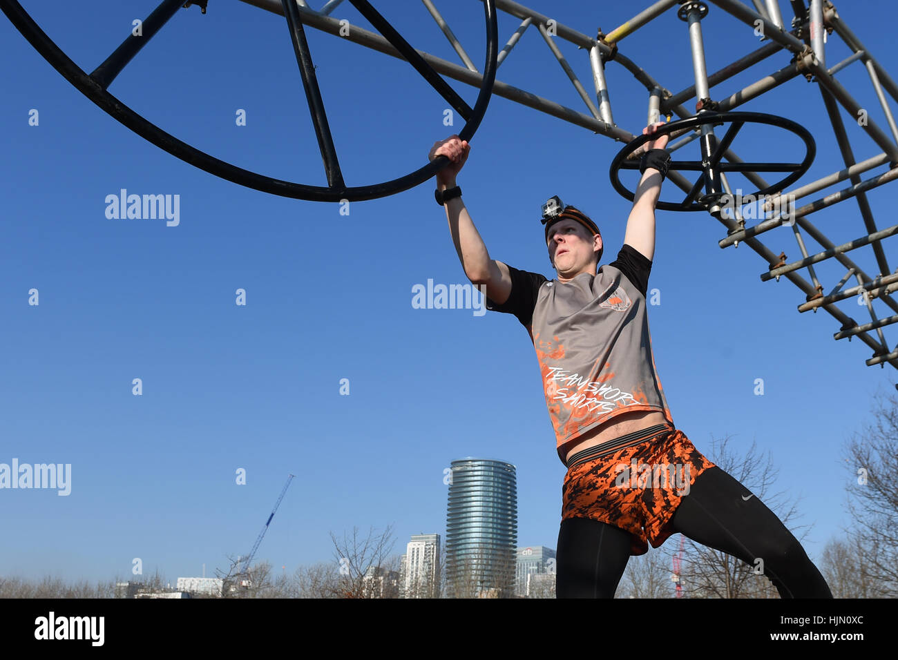 A competitor tackles an obstacle at Mudchute Park and Farm after Tough Mudder transformed Mudchute DLR station in - Stock Image
