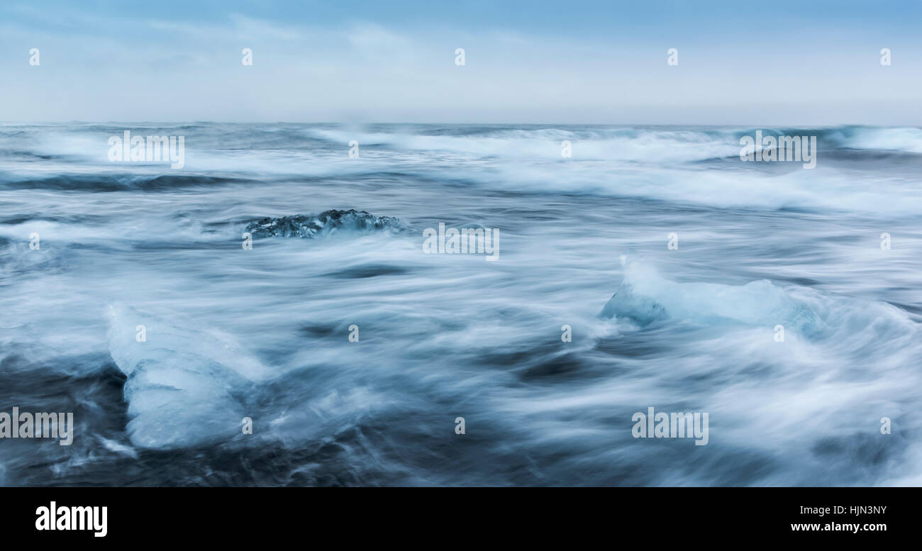 Moving sea around small ice bergs in Iceland - Stock Image