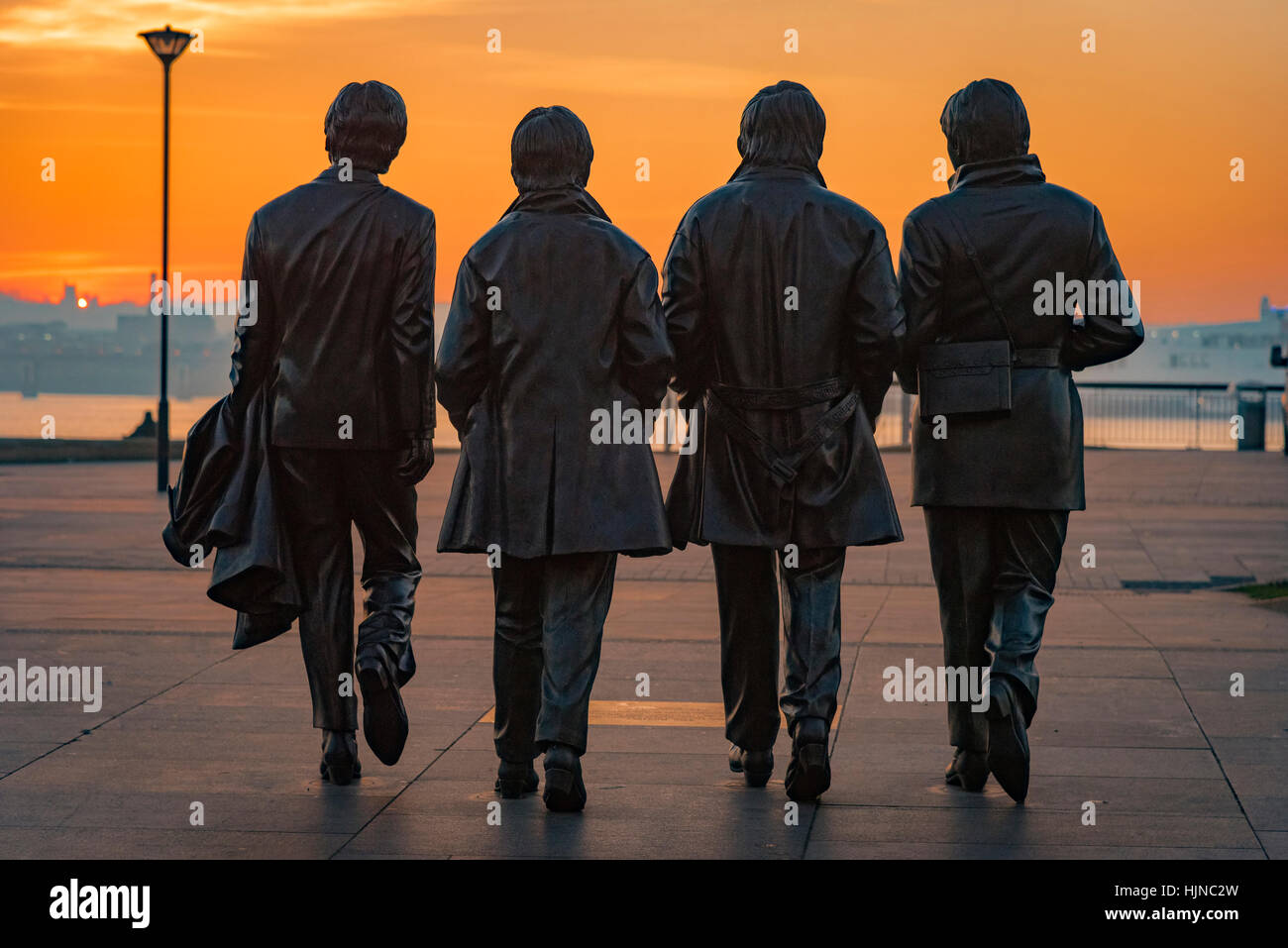 Statue of the Beatles or Fab Four at Liverpool pierhead in the evening sun. - Stock Image