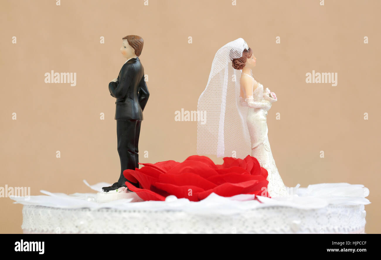 A divorced couple on top of a wedding cake - Stock Image