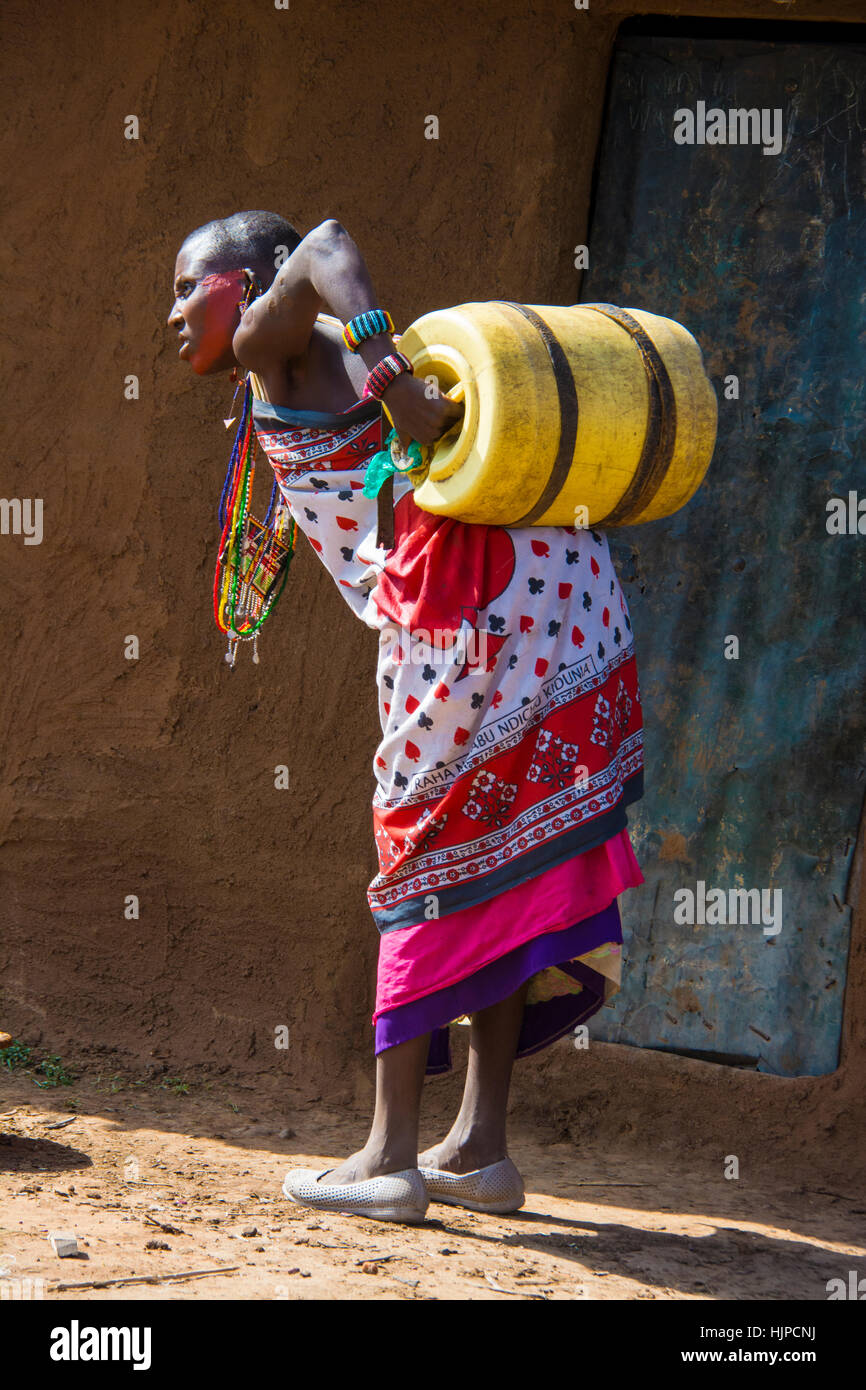 Maasai Woman struggling with a water barrel on back, wearing traditional attire, in a village near the Masai Mara Stock Photo
