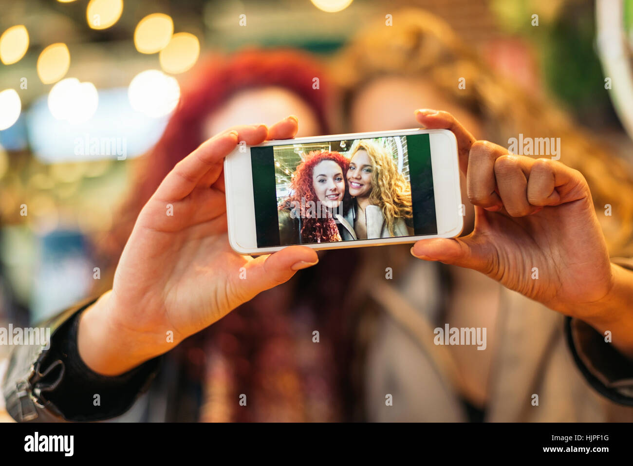 Young friends taking a selfie with cellphone in a restaurant bar - Stock Image