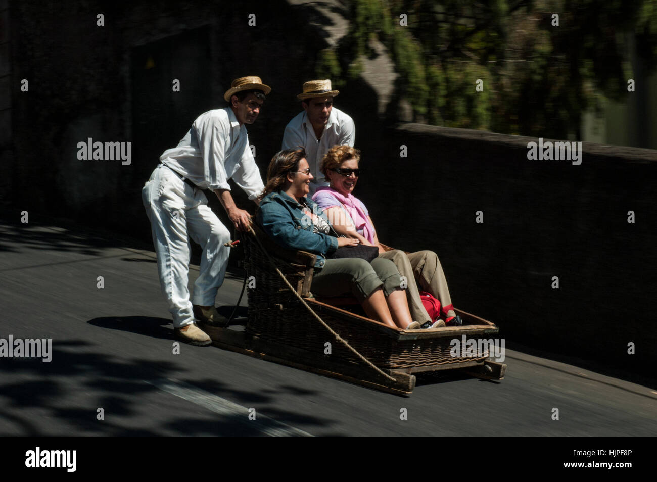 Tourists  being pushed in wicker toboggan Monte. Funchal, Madeira, Portugal - Stock Image