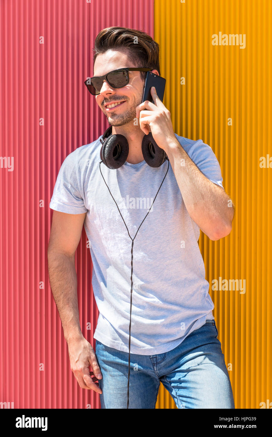 Portrait of handsome man in urban background talking on phone - Stock Image