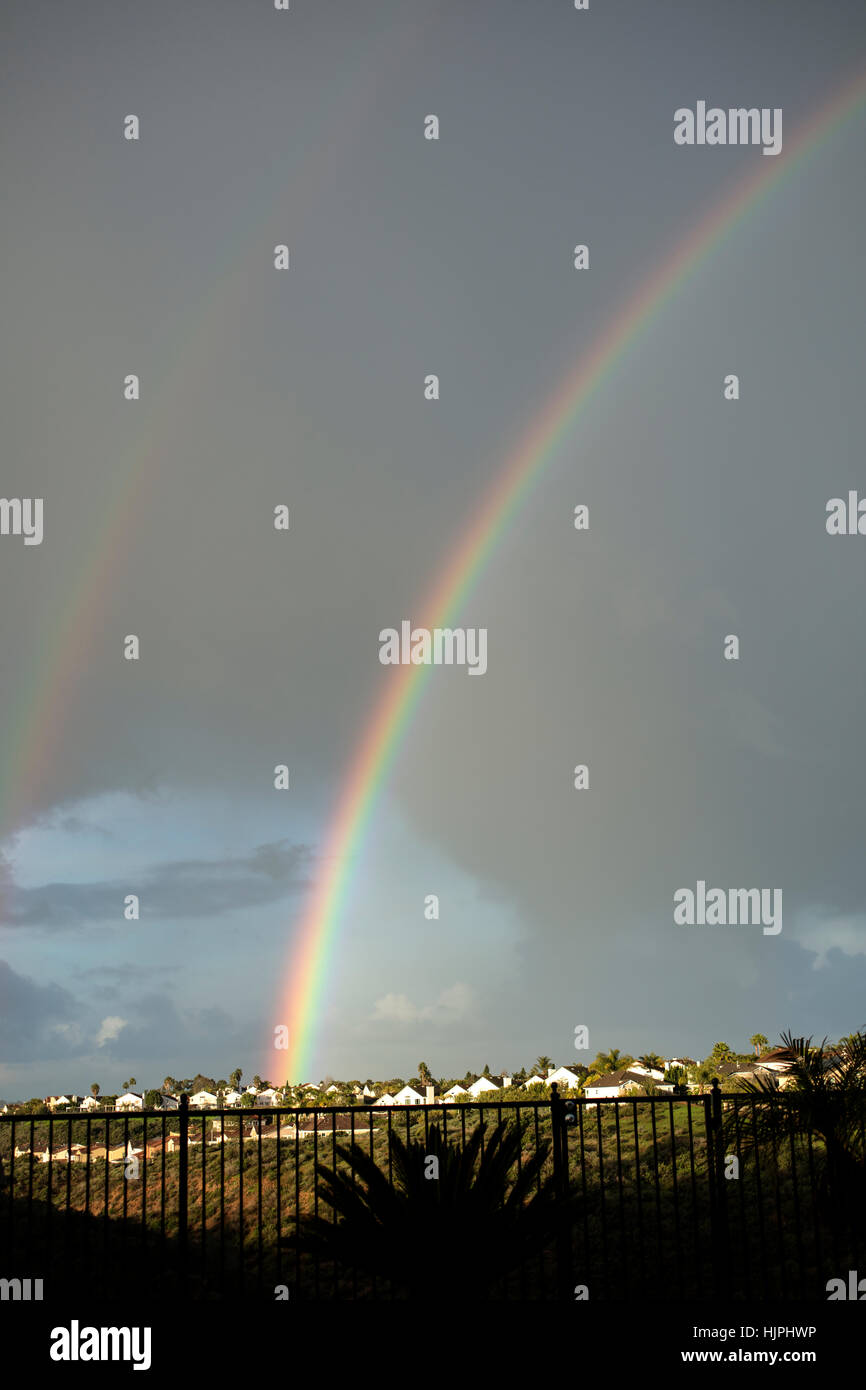 Large rainbow arching over a residential area surrounded by storm clouds - Stock Image