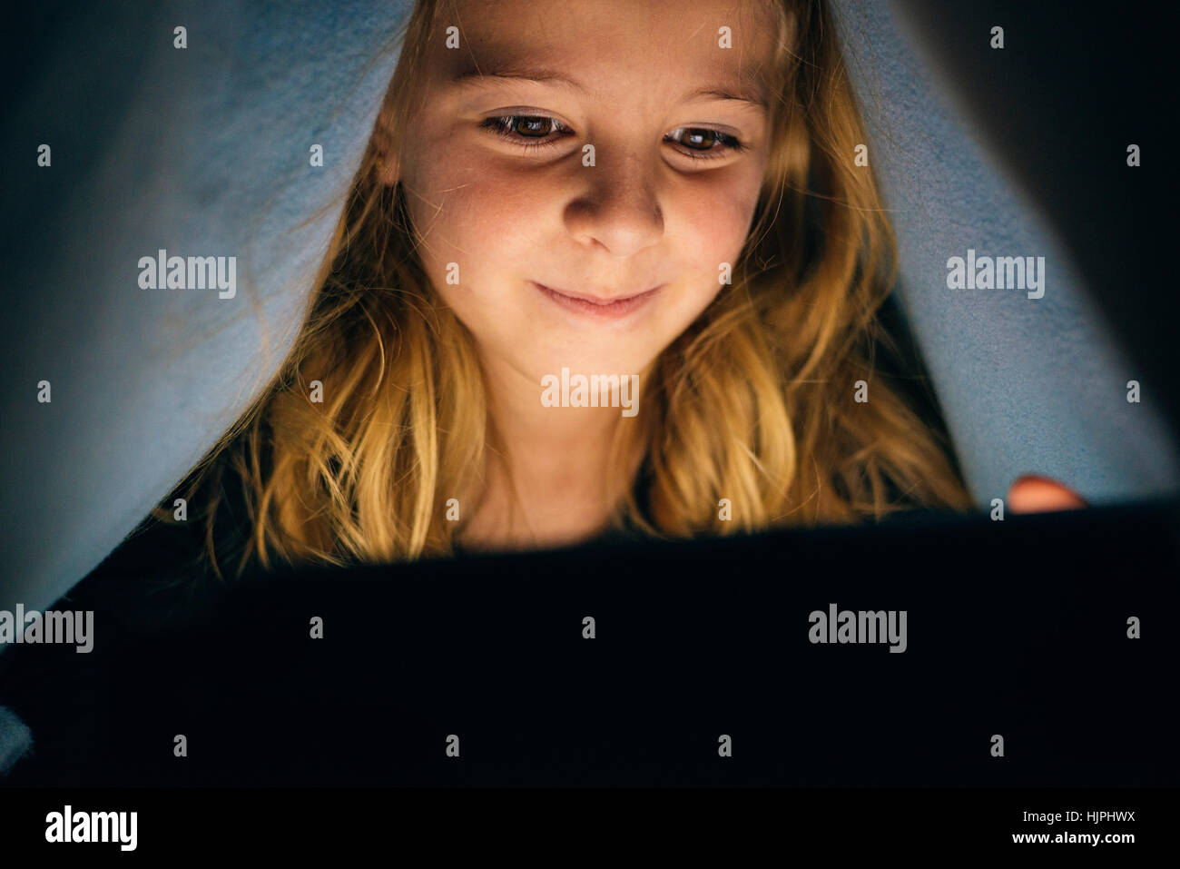 Sweet blondie girl playing on a Tablet PC. - Stock Image