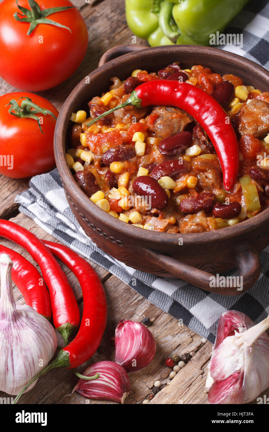 Mexican food chili con carne in a pot and ingredients. vertical view from above - Stock Image