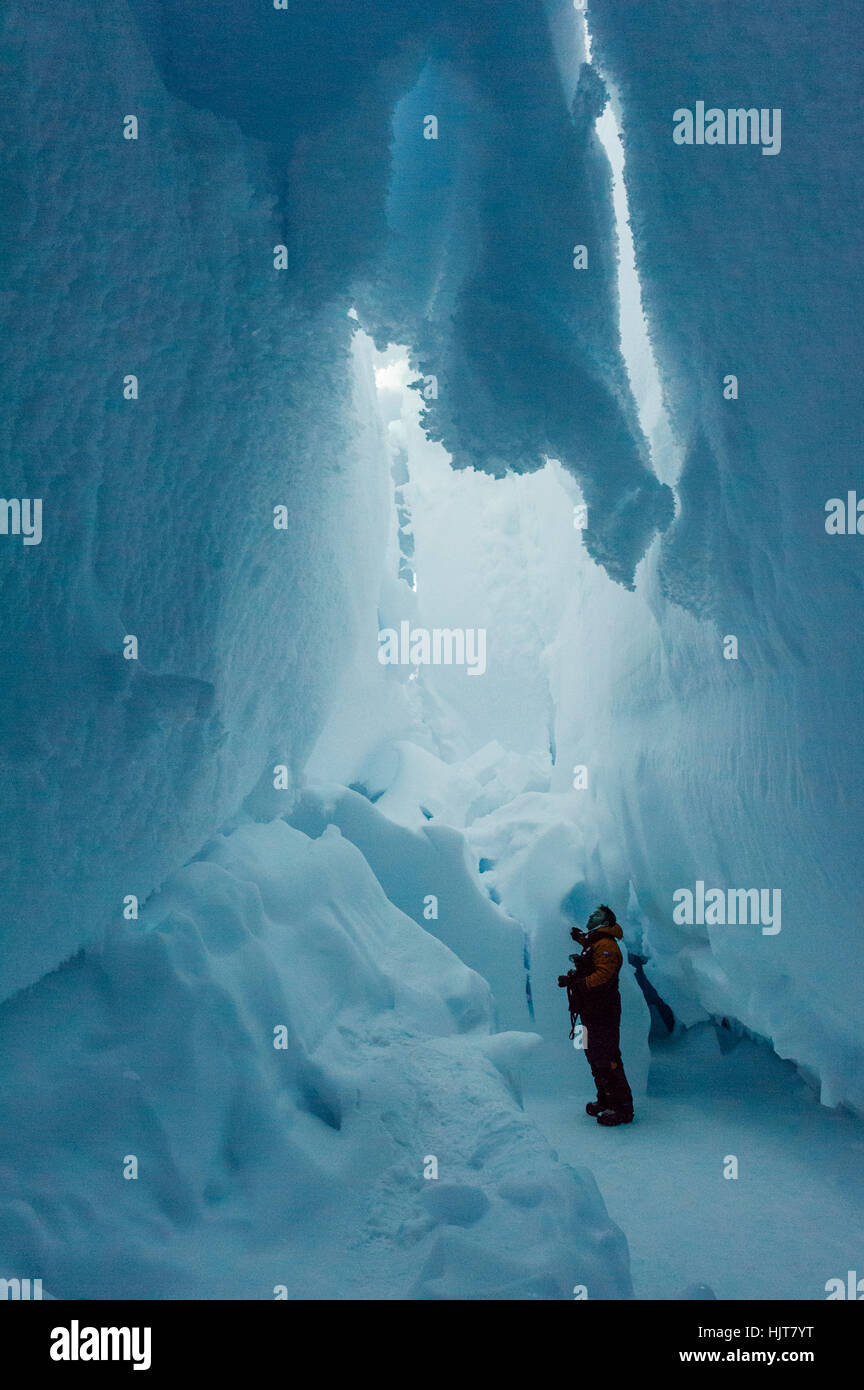 A photographer examines the frozen ceiling and icy walls of an ice cave in the Erebus Glacier Tongue. - Stock Image