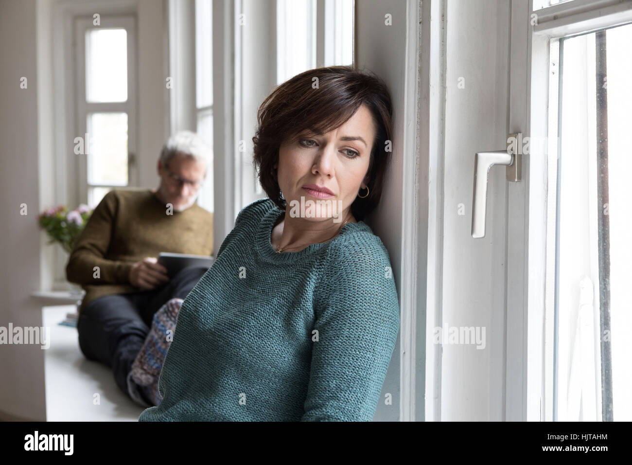 Disappointed woman with man in background - Stock Image