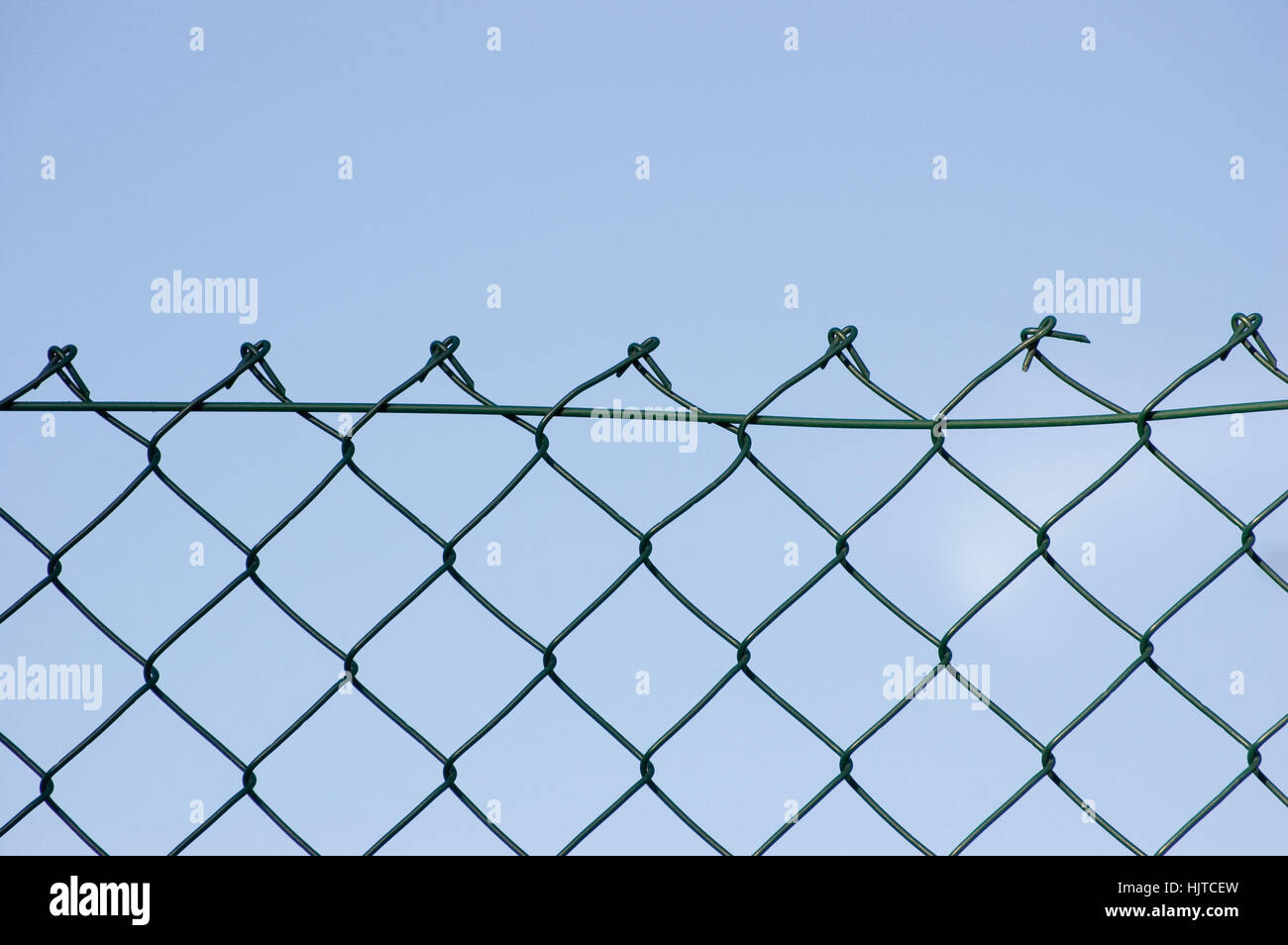 New wire security fence over bright blue sky horizontal closeup - Stock Image