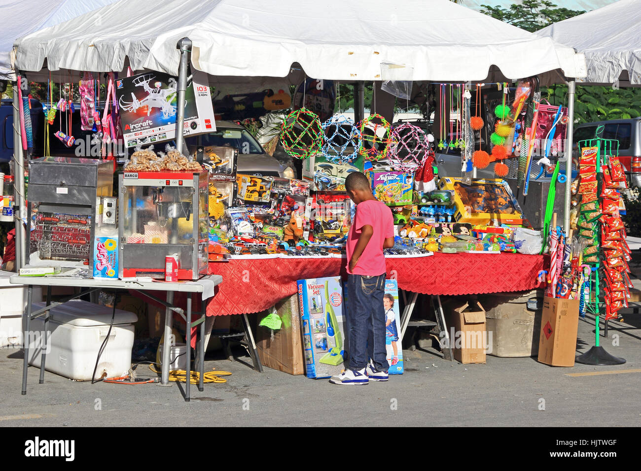 Boy looking at toys on market stall, Road Town, Tortola - Stock Image