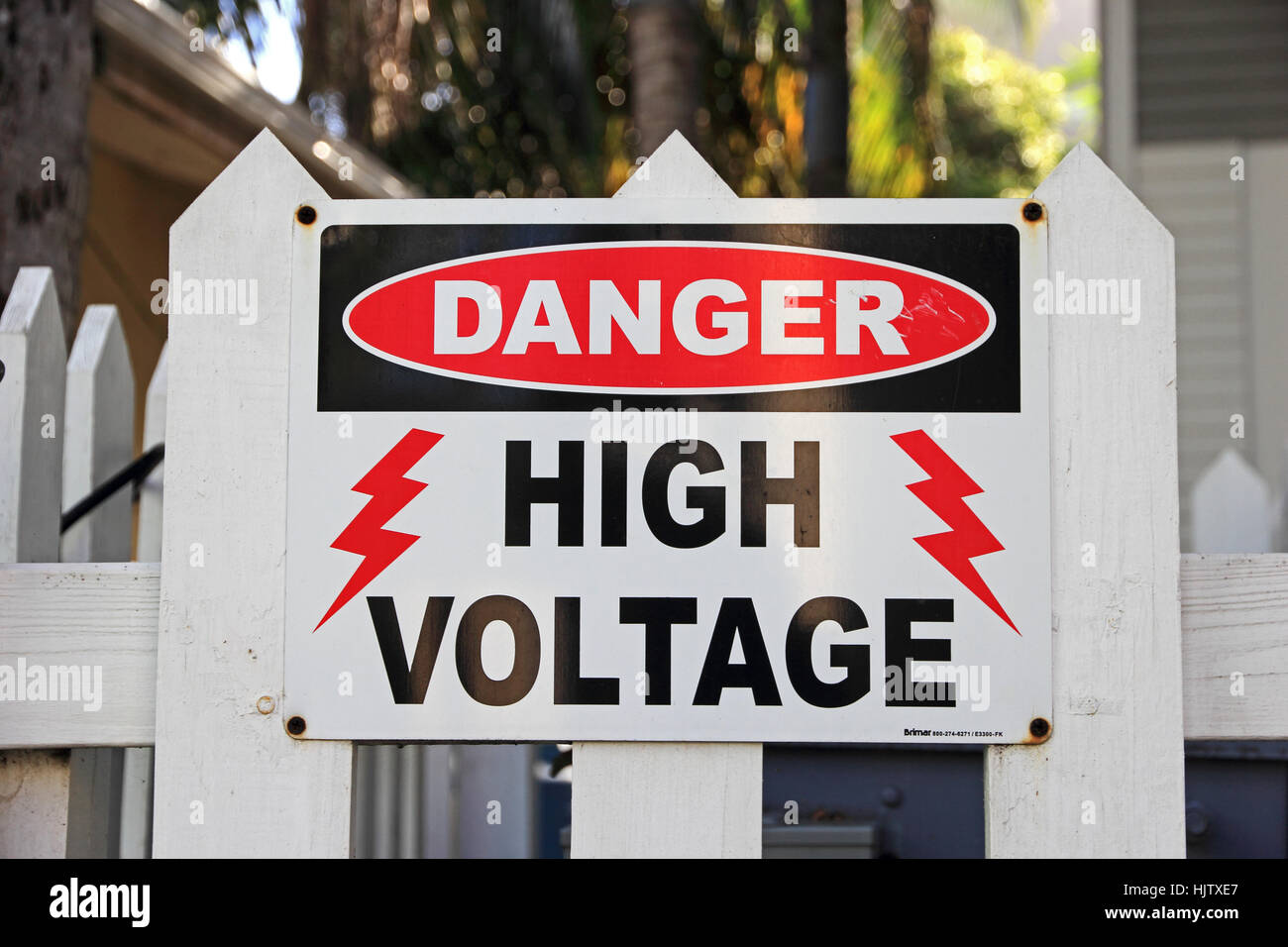 Danger High Voltage sign on white picket fence Stock Photo ...