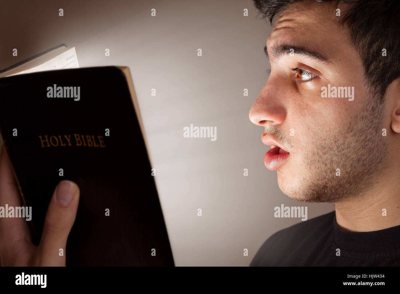 Young man astonished and intrigued by open Bible - Stock Image