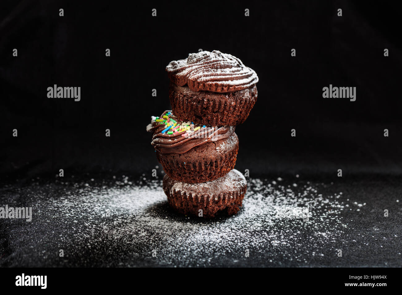 A pile of cakes on a black background - Stock Image