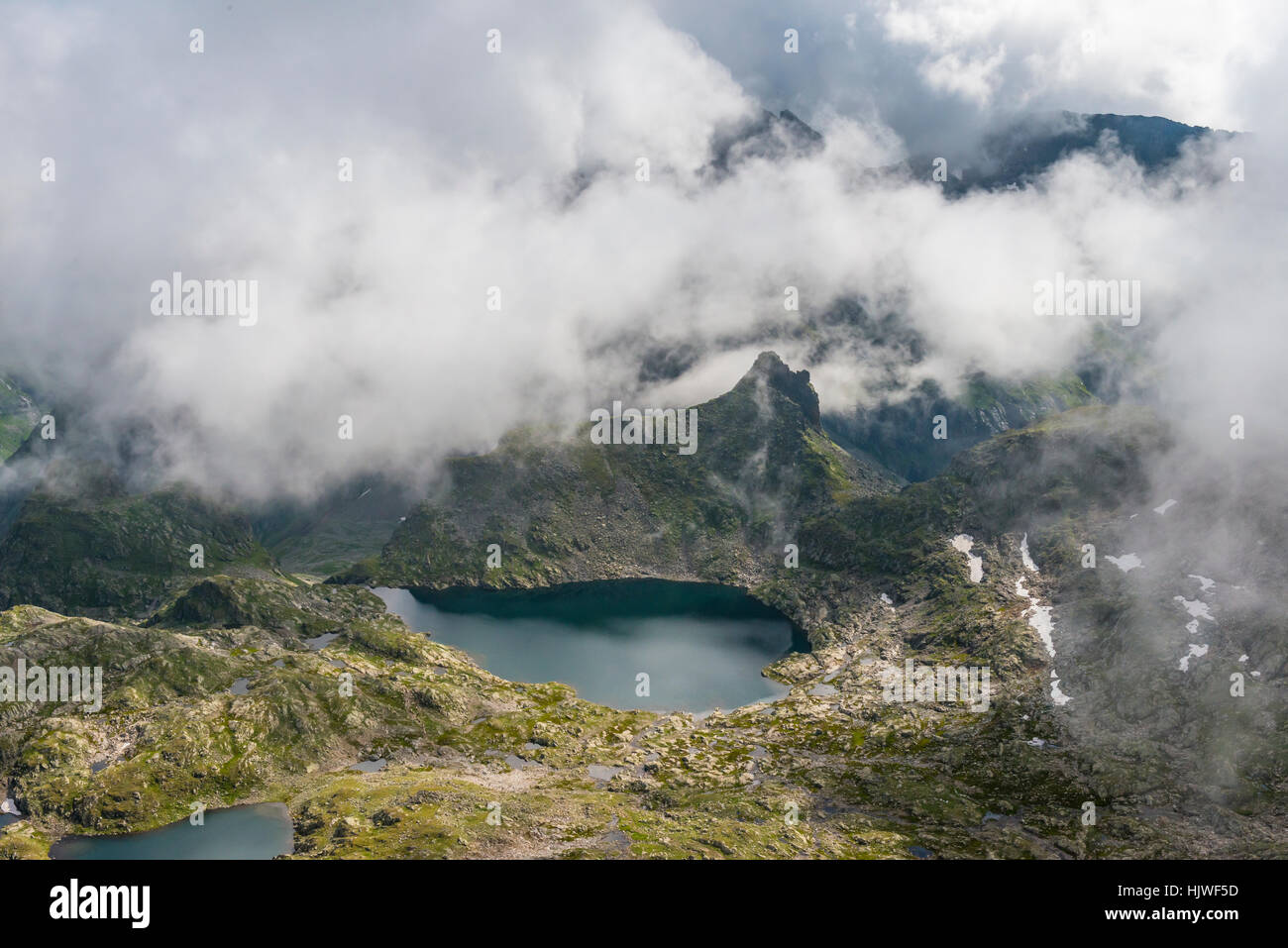 Clouds passing over a ridge by a mountain lake, view from Greifenberg, Upper Klaffersee, Klafferkessel, Schladminger Stock Photo