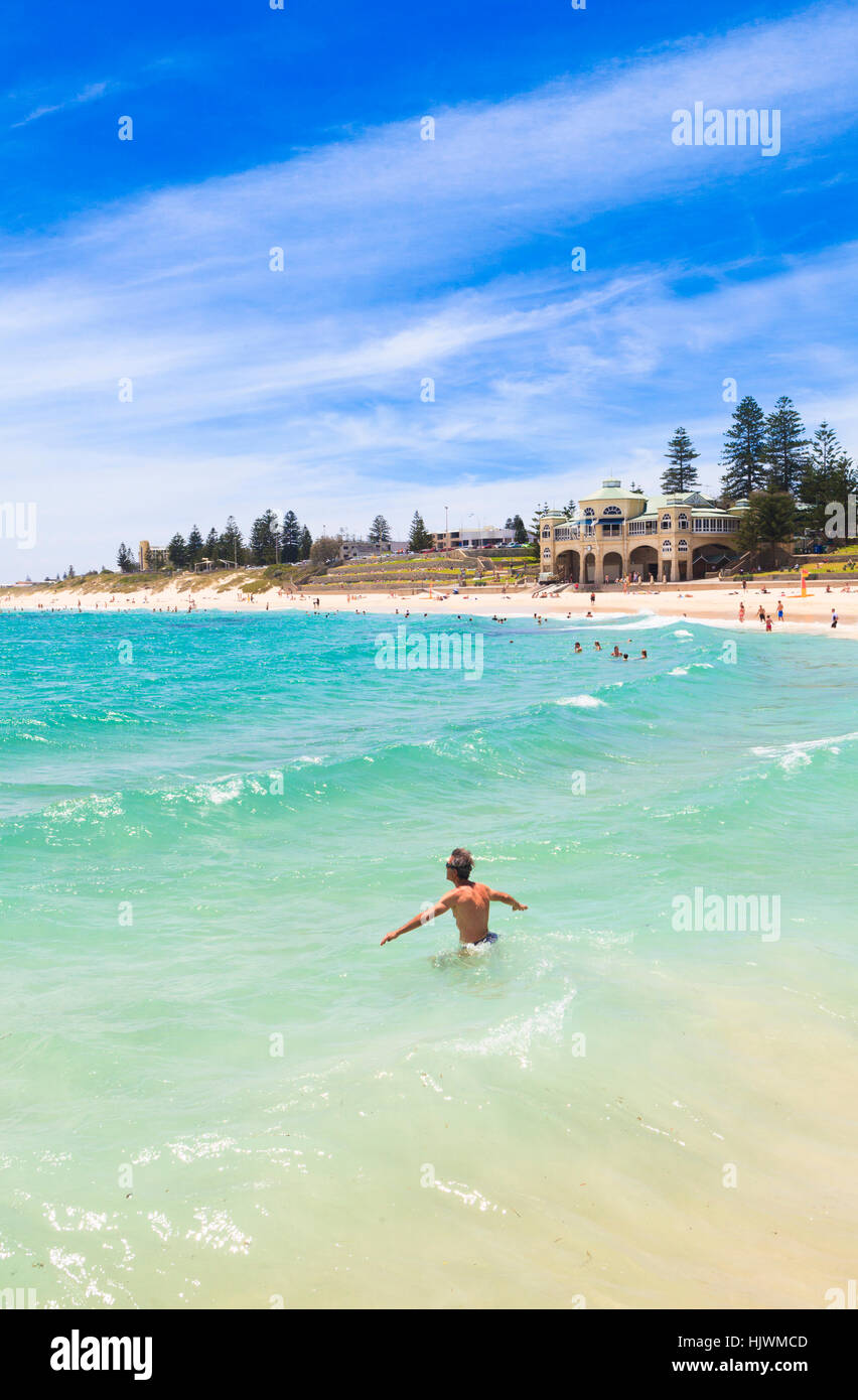 A man wading out to sea at Cottesloe Beach in Perth, Western Australia - Stock Image