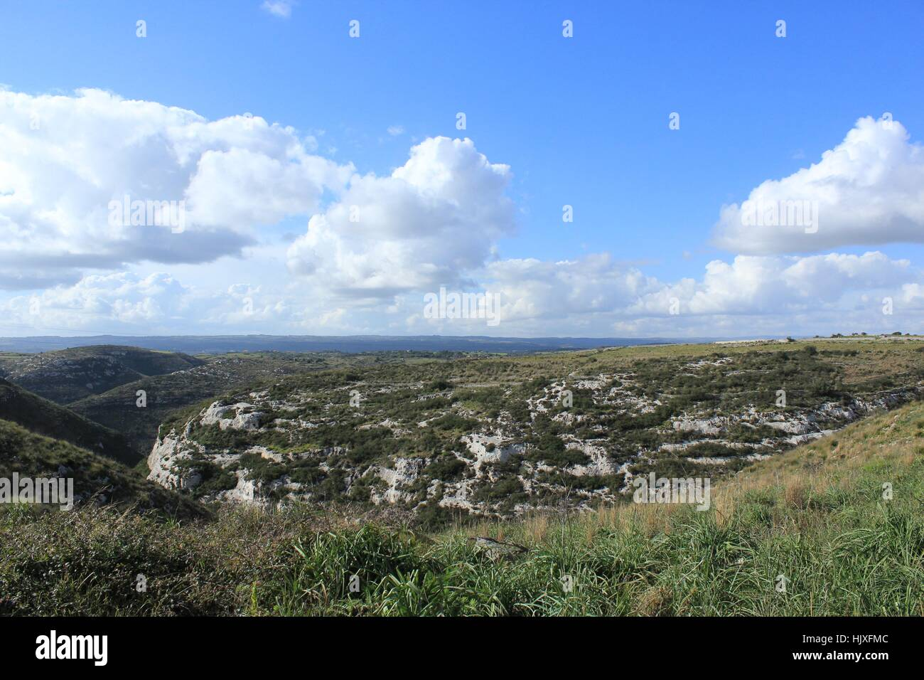 Cumulonimbus clouds float in a blue sky over the rolling hills of Sicily. - Stock Image