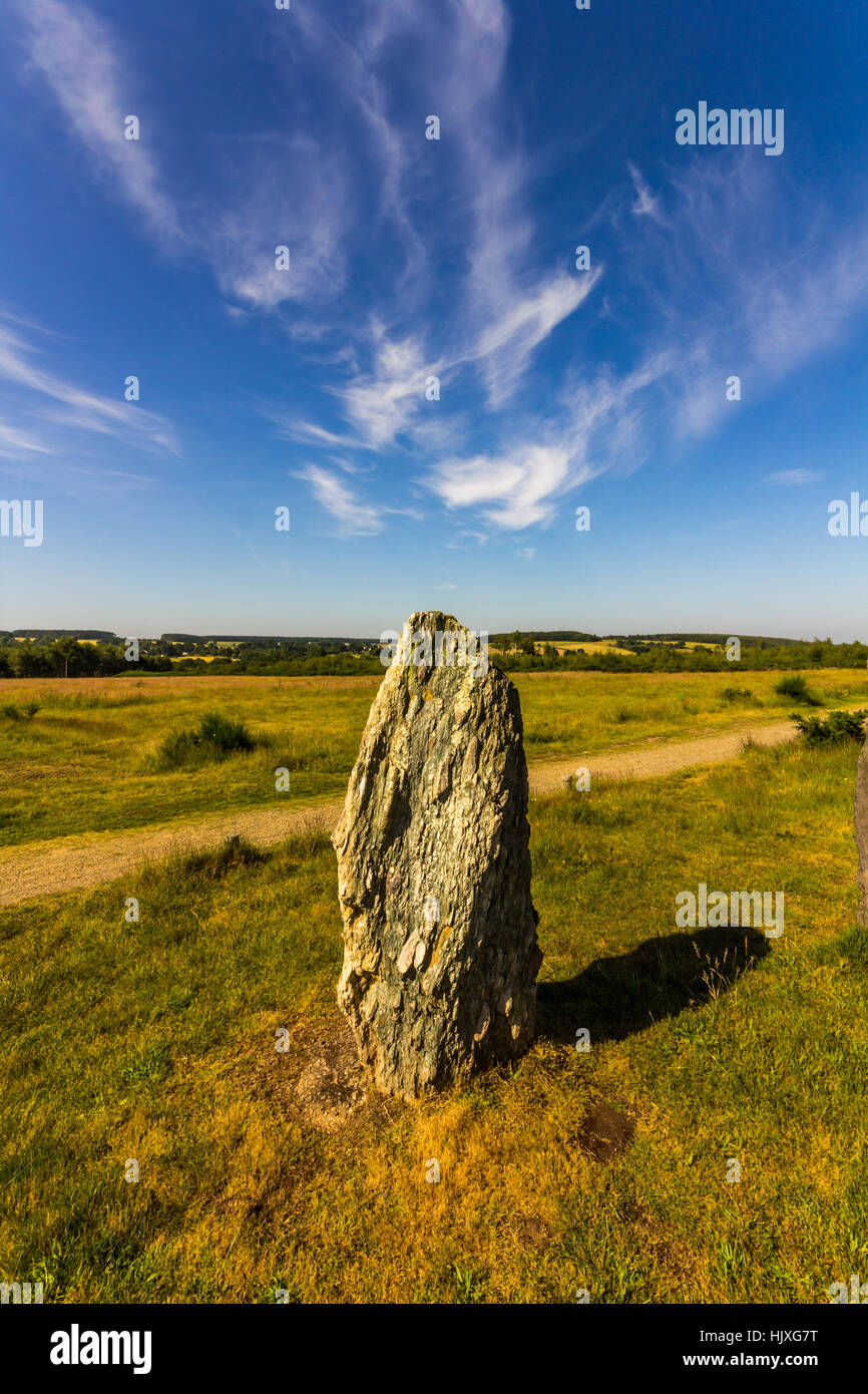 standing stones in a green field with blue sky and wispy clouds - Stock Image