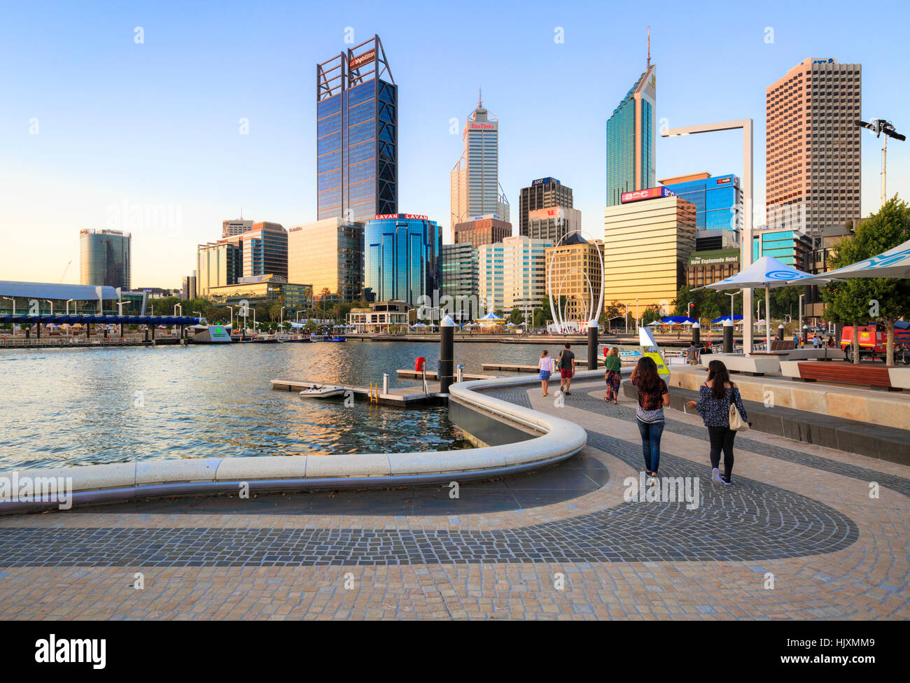 People walking along along a footpath beside the Swan River at Elizabeth Quay. - Stock Image