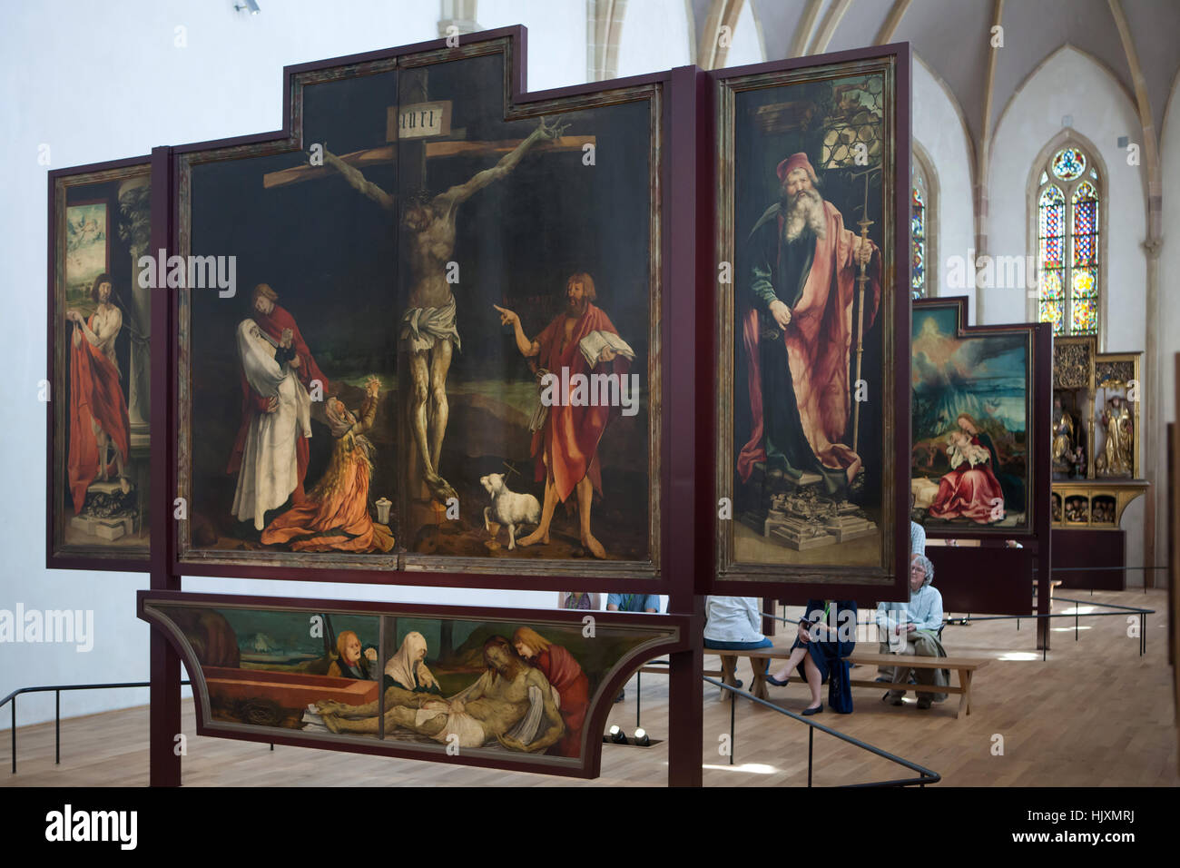 Visitors in front of the Isenheim Altarpiece (1512–1516) by German Renaissance painter Matthias Grunewald displayed Stock Photo