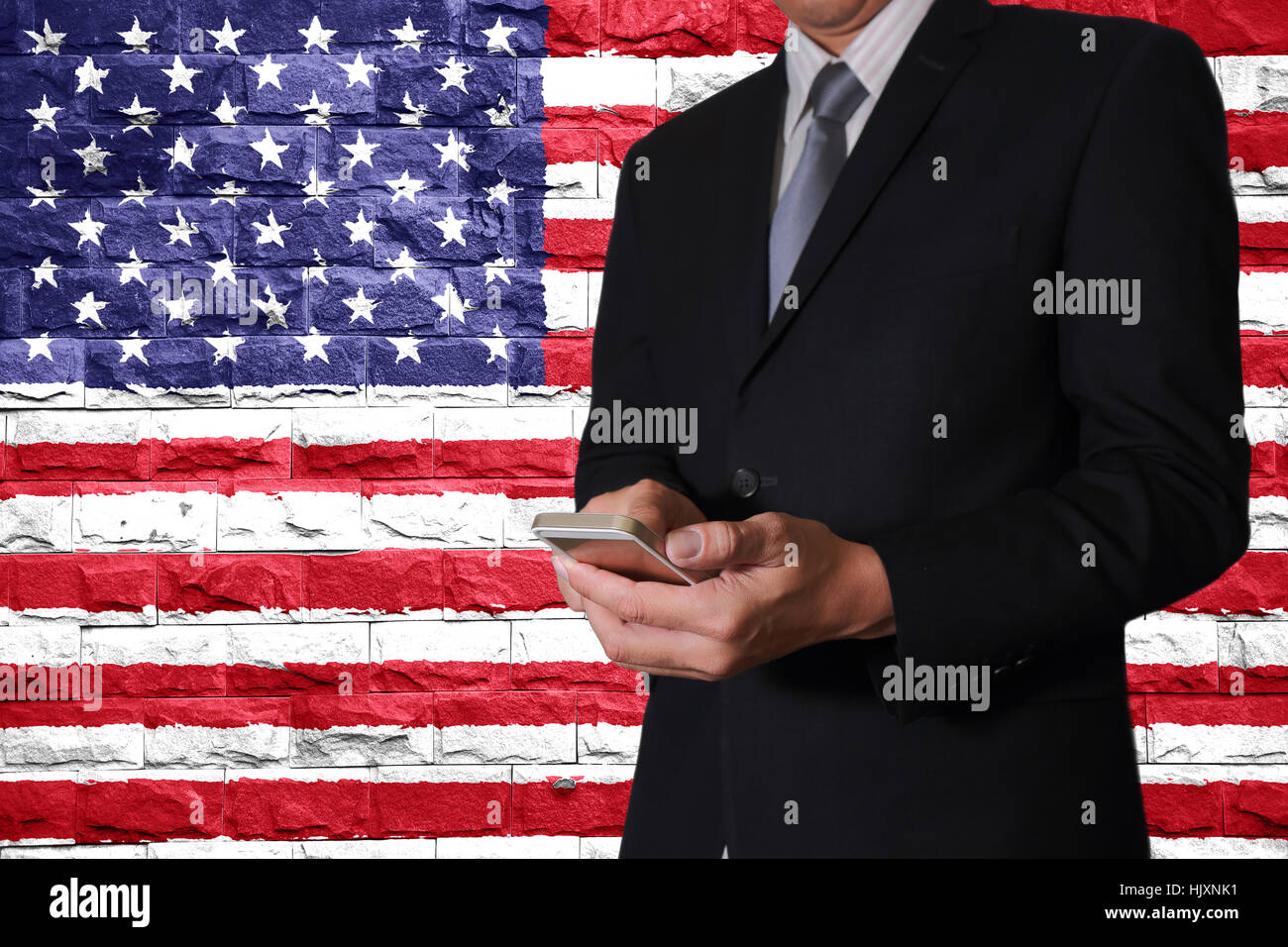 Business man hand touch screen smart phone and brick Walls are painted United States flag (USA) as communication Stock Photo