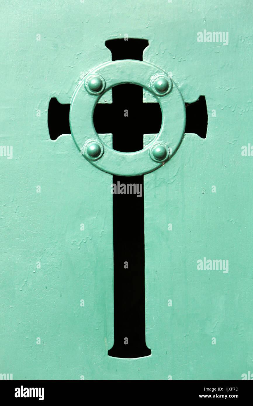 Cross on a green door of a vault. - Stock Image