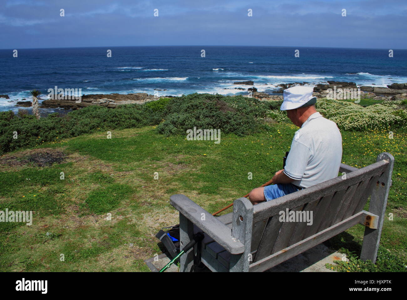 Old man sits next to the sea deep in thought image in landscape format with copy space - Stock Image