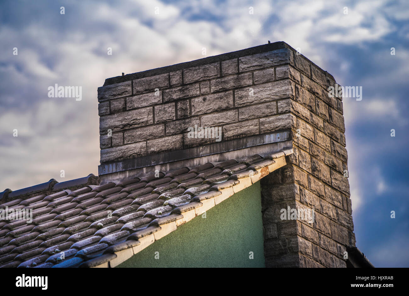 Chimney closeup in front of a cloudy sky - Stock Image
