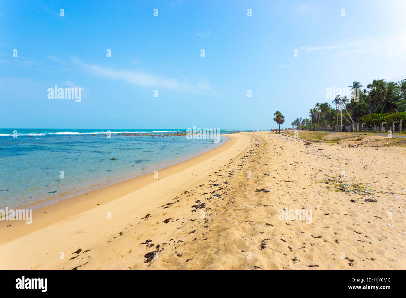 A sand beach with strewn litter seen in Point Pedro, along the northern coast of Jaffna, Sri Lanka. Horizontal - Stock Image