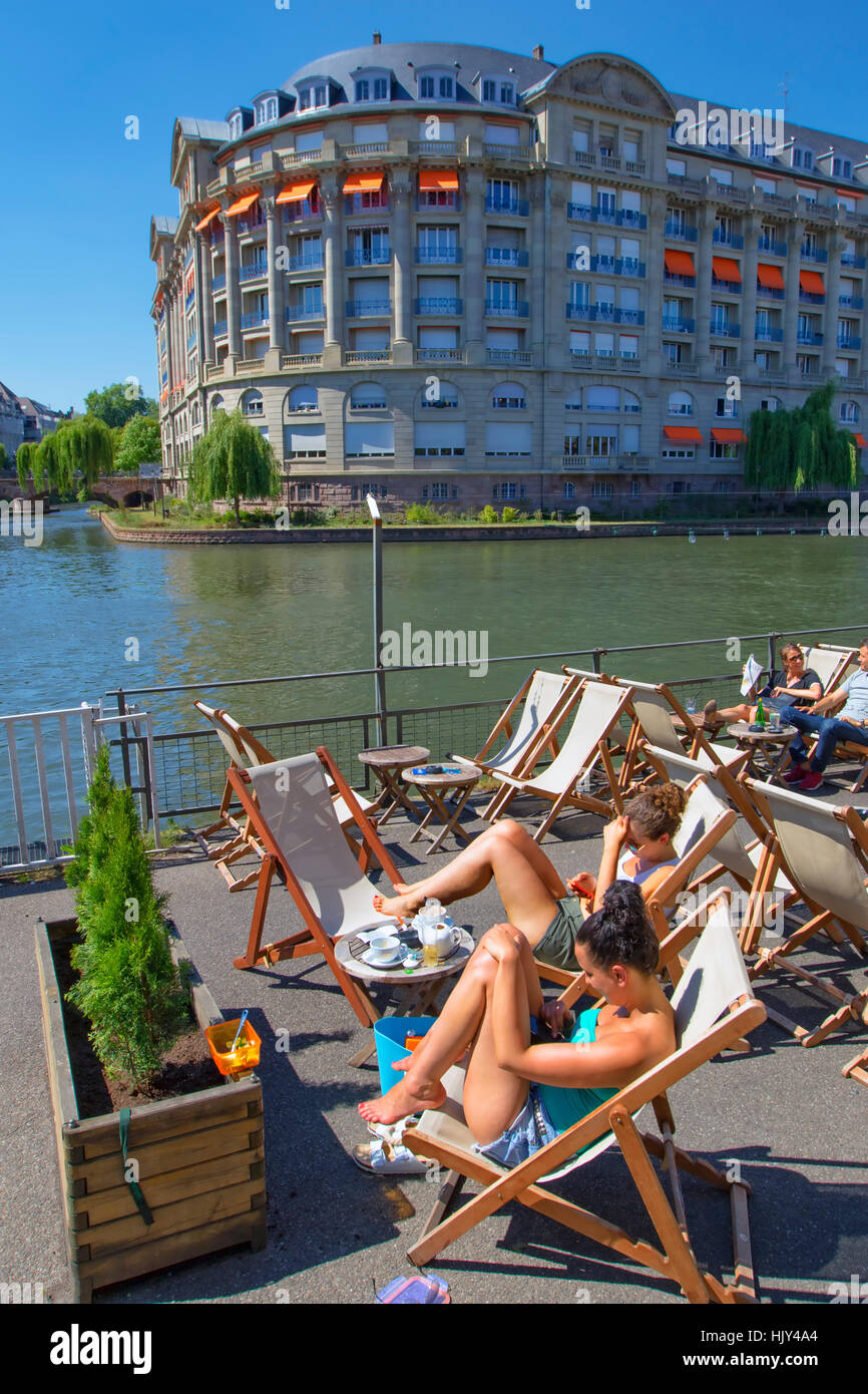 People relaxing in a cafe along river Ill, Strasbourg - Stock Image
