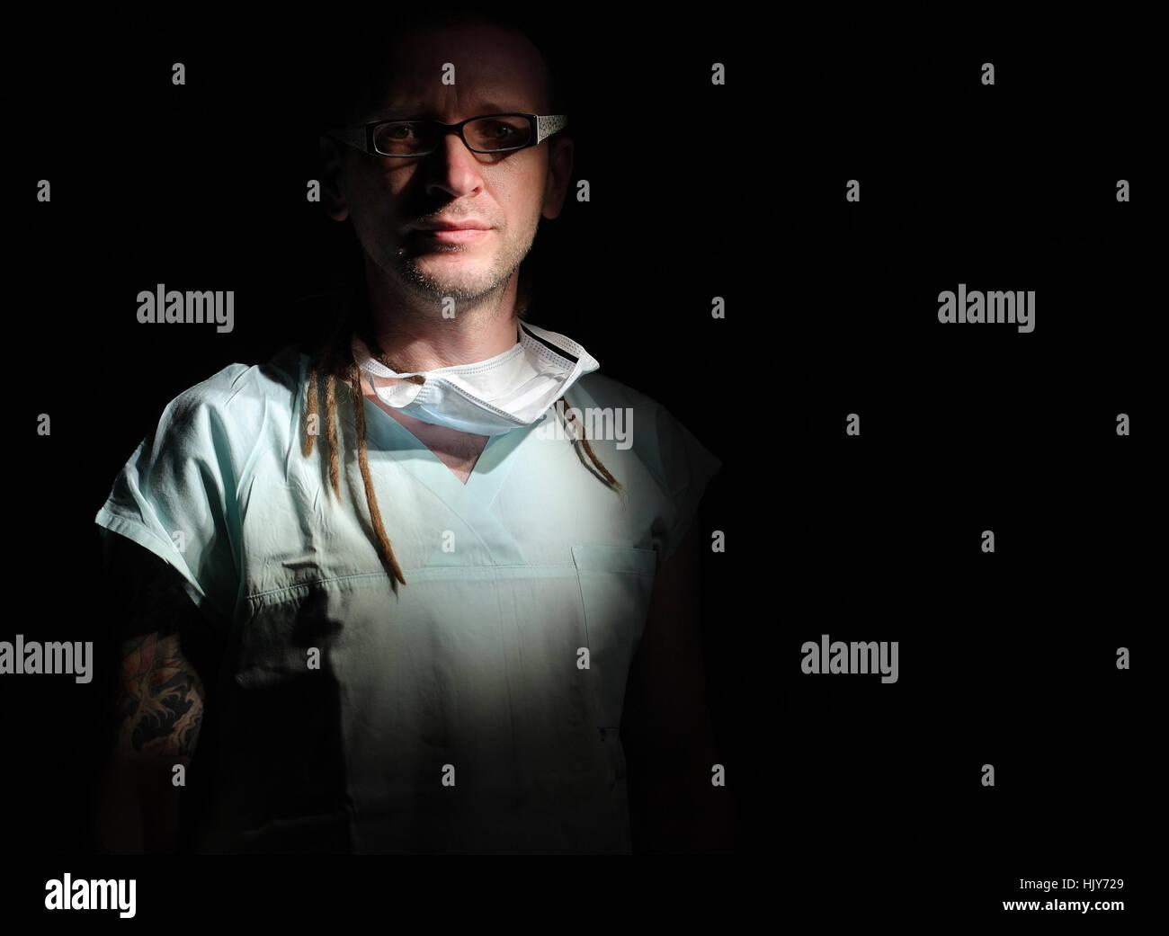 Portrait of  male nurse ICU  with tattoo and dreadlocks on black background - Stock Image