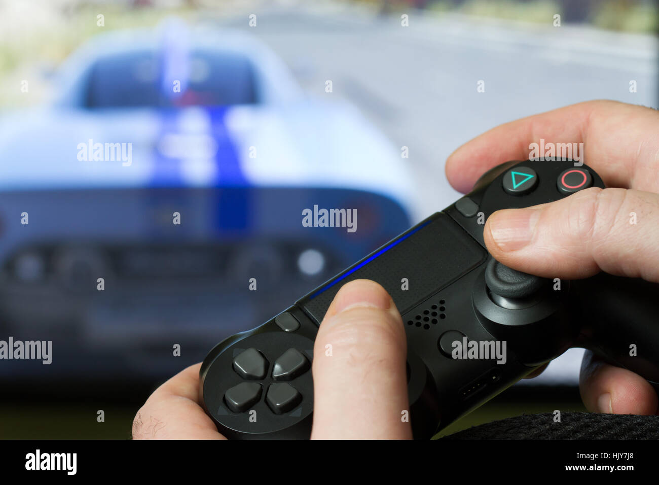 Video game controller from the console against the monitor screen - Stock Image