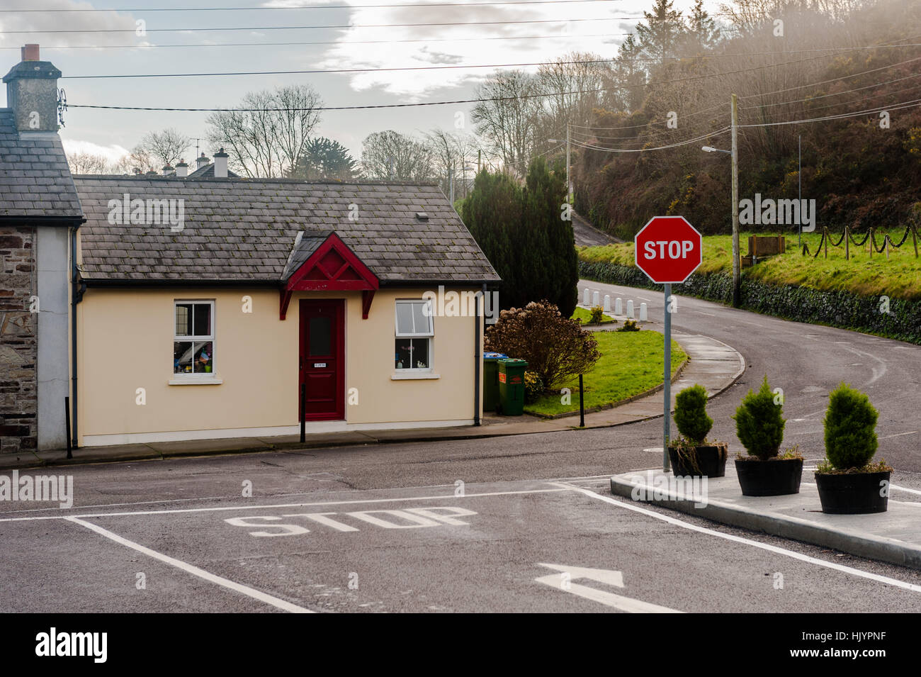 A picturesque bungalow at a road junction with a stop sign and copy space in West Cork, Ireland. - Stock Image
