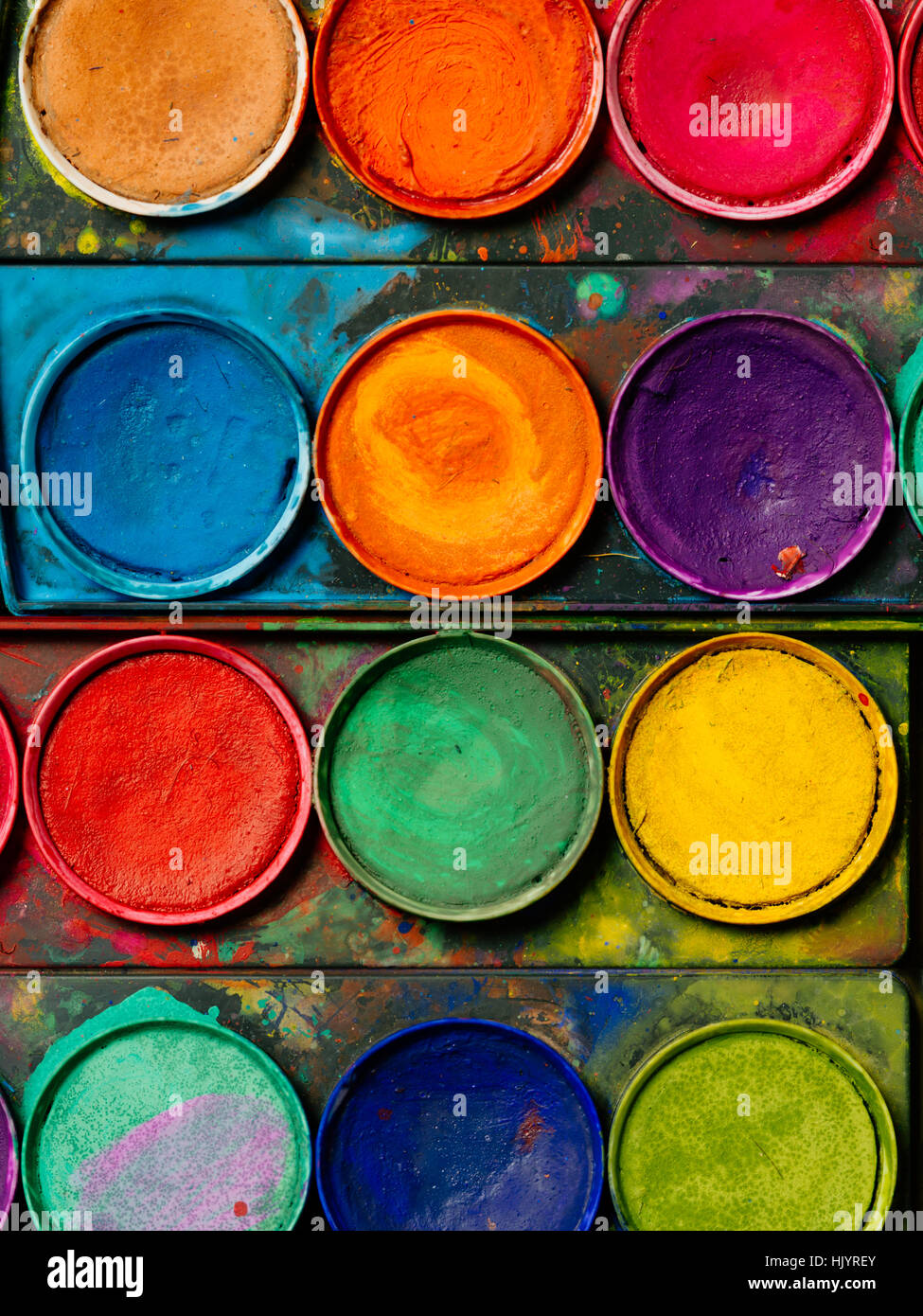 Photo of a palette of watercolor paints and well-used tray. - Stock Image