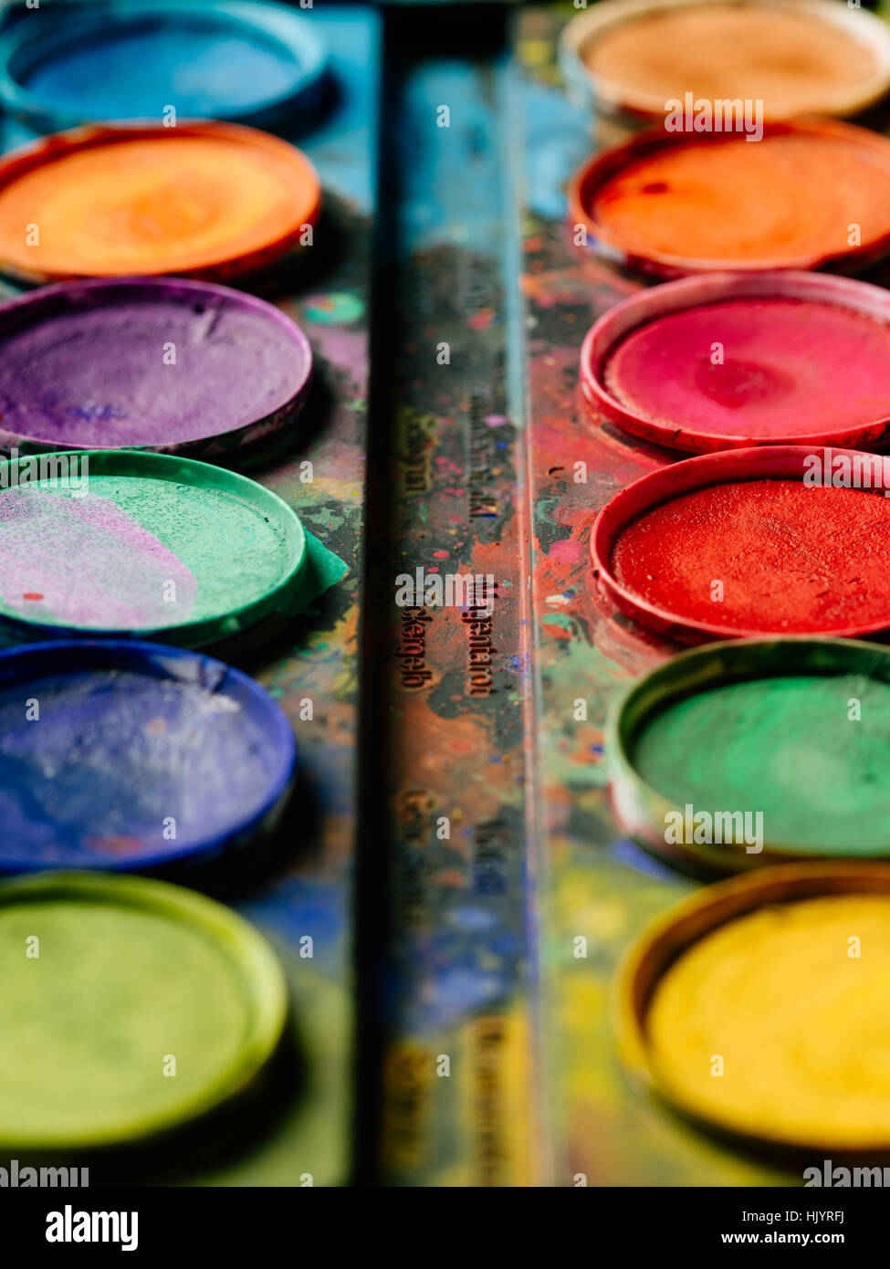 Photo of a palette of watercolor paints on a well-used tray. - Stock Image