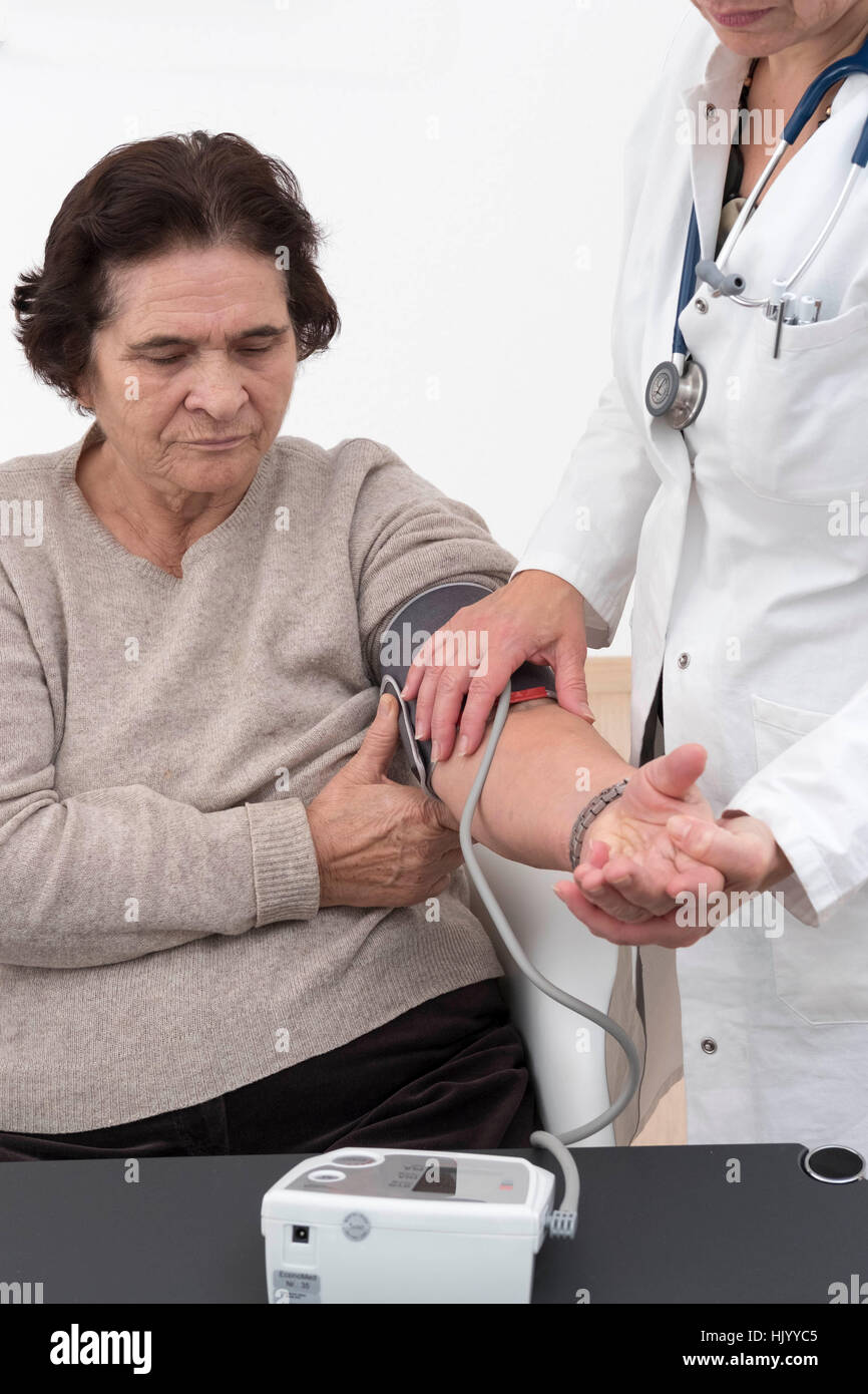 Doctor checks blood pressure of senior female patient - Stock Image