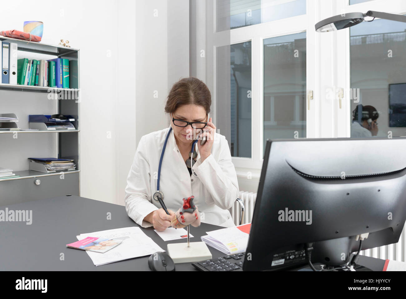 Female doctor  consulting patients over the telephone - Stock Image