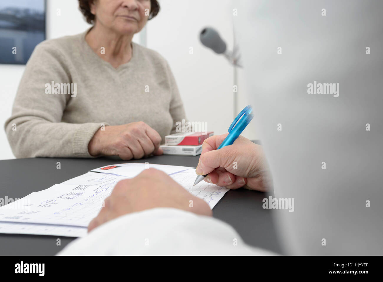 Doctor consulting  senior female patient-cardiologist explaining ECG results to senior female patient - Stock Image