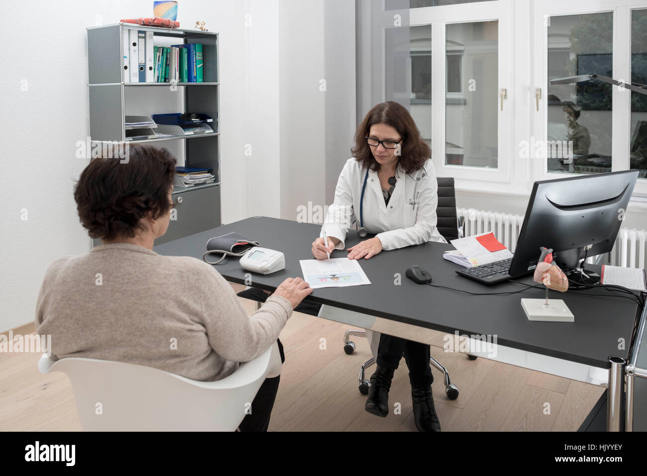Doctor consulting senior female patient - Stock Image