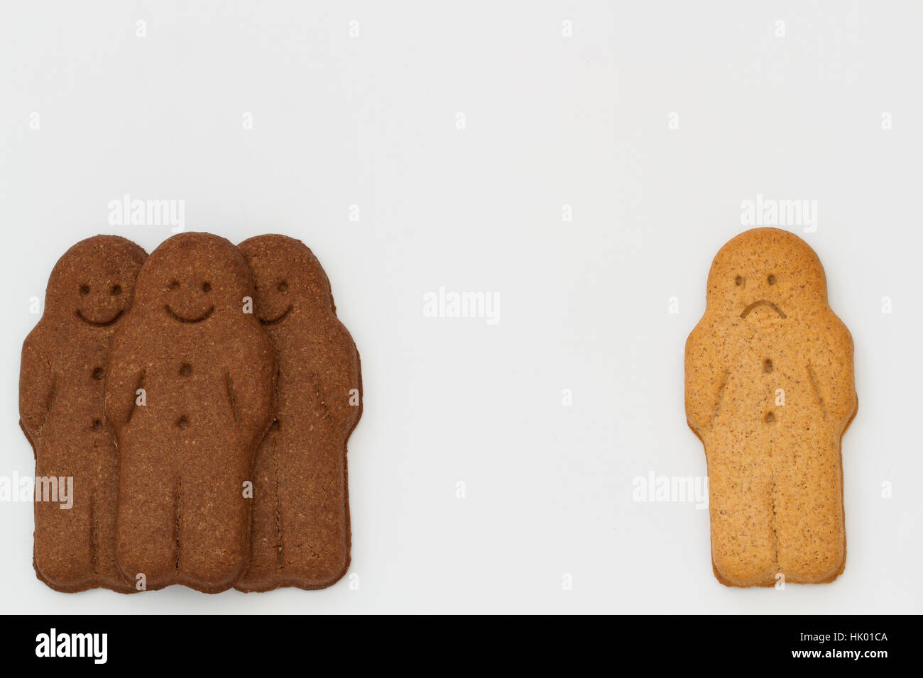 Groups of black and white gingerbread with a person isolated from the group representing racial discord and division. - Stock Image