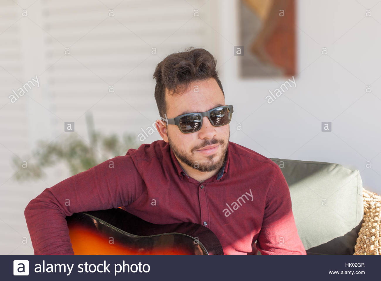 Young man with sunglasses playing acoustical guitar - Stock Photo